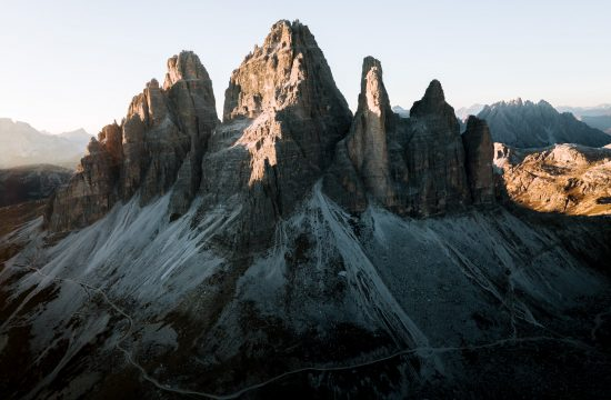 A beautiful sunset lights up the landscape in the Italian Dolomites shining a warm, orange light on the Tre Cime mountains. By photographer Michael Schauer